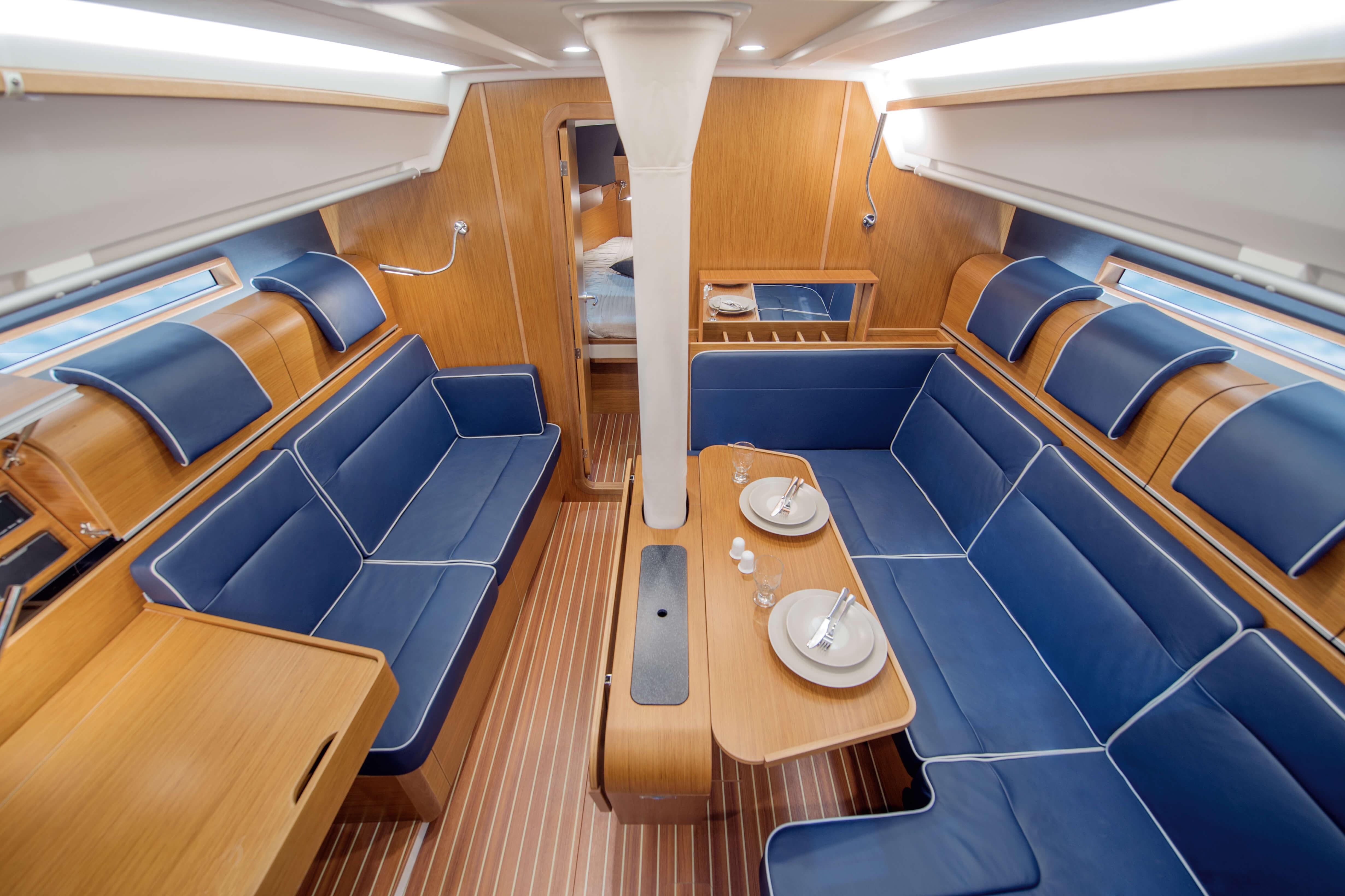 Dehler 42 Interno salone | B1 Layout: teak, zona di seduta, tavolo pieghevole, finestra, portello della coperta, portabottiglie | Dehler