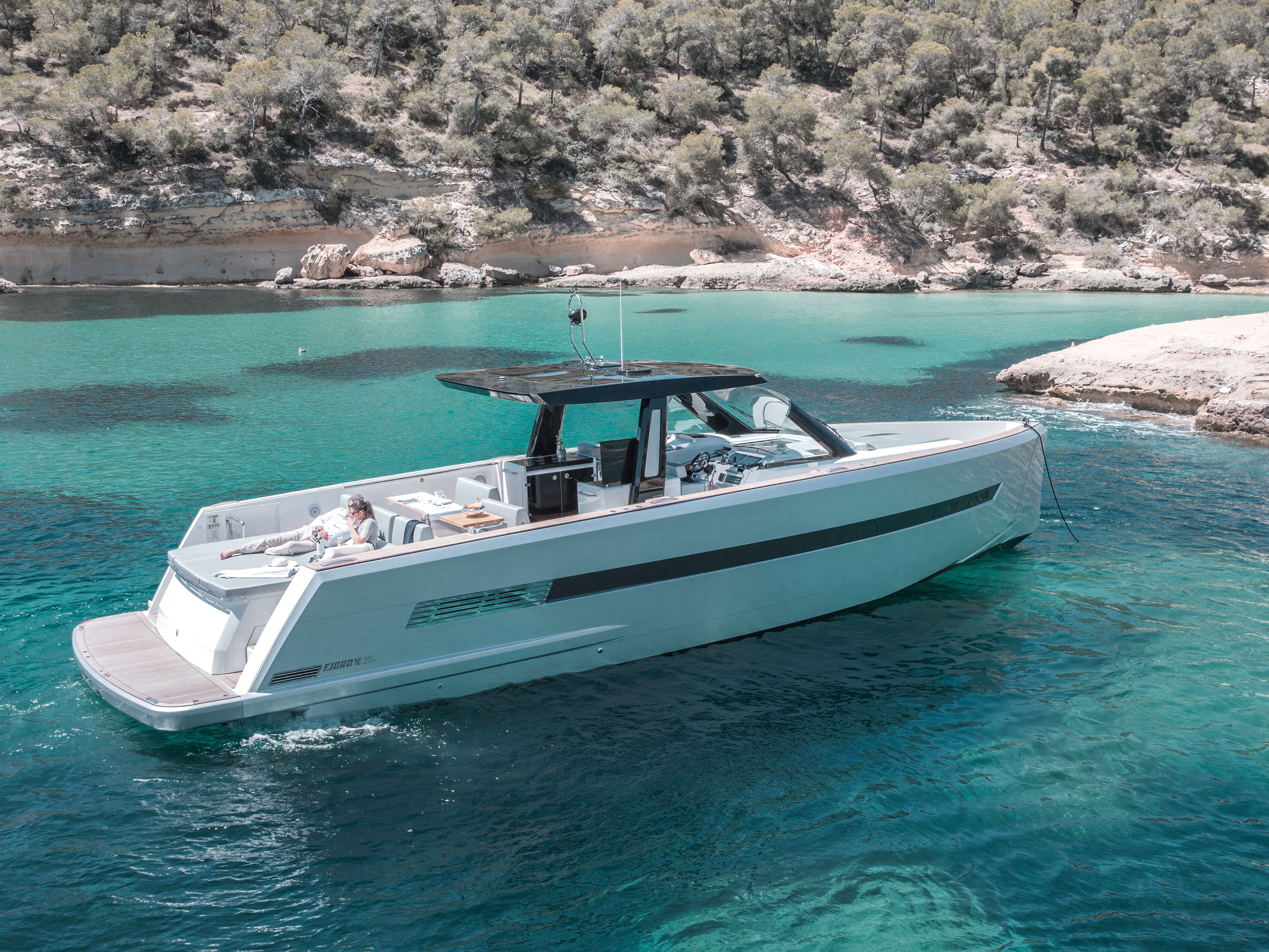 Fjord 48 open Exterior at anchor | painted hull, T-top with skylights, sitting area with foldable table convertible to sunbed, aft sunbed, bathing platform with teak and hydraulic lift, ladder connecting main deck and bathing platform | Fjord