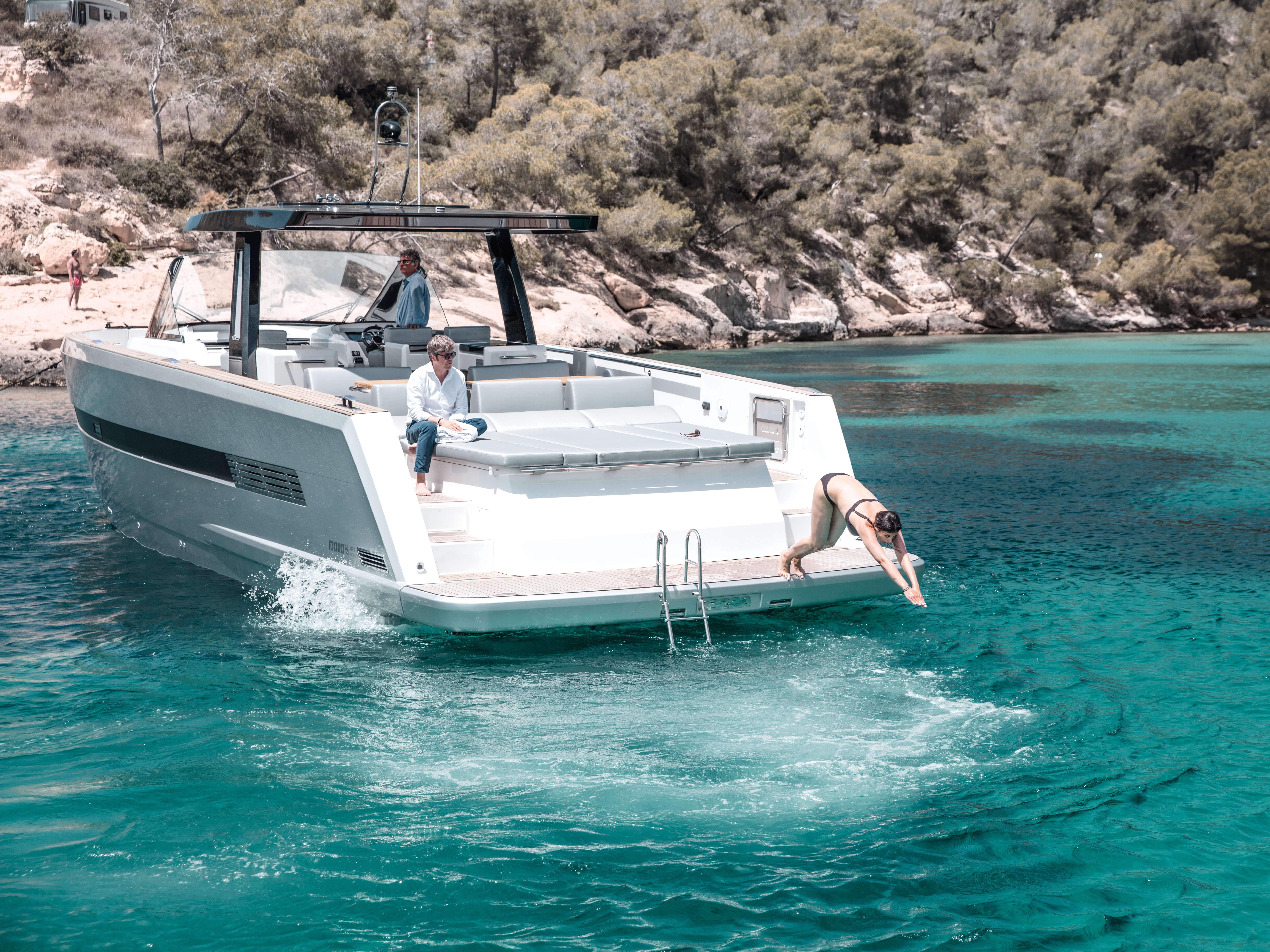 Fjord 48 open Exterior ride | bathing platform with teak and hydraulic lift, stand alone bathing ladder with handles, aft sunbed, painted hull, T-top with skylights | Fjord