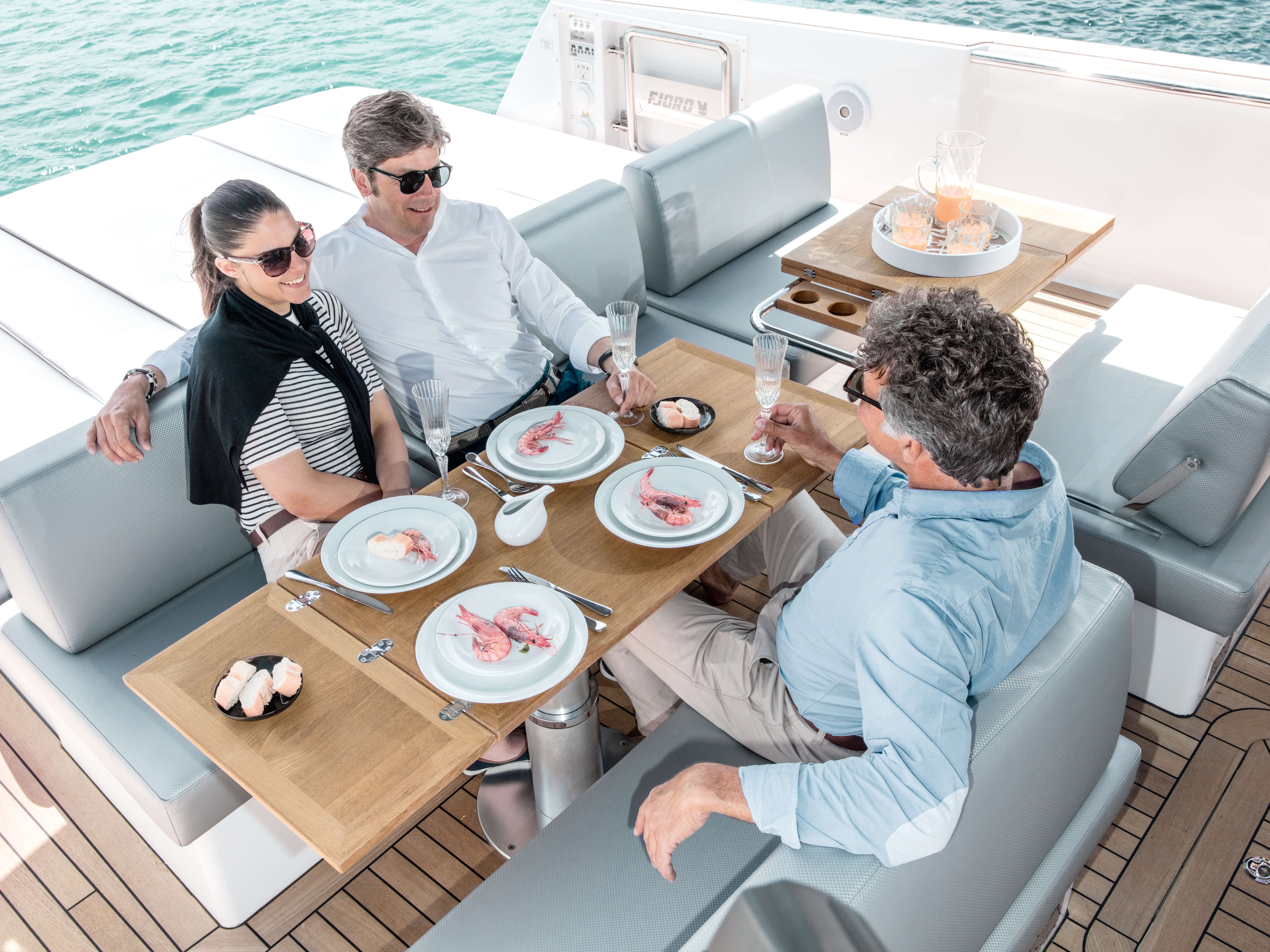 Fjord 48 open Exterior at anchor | sitting area with foldable table convertible to sun bed | Fjord