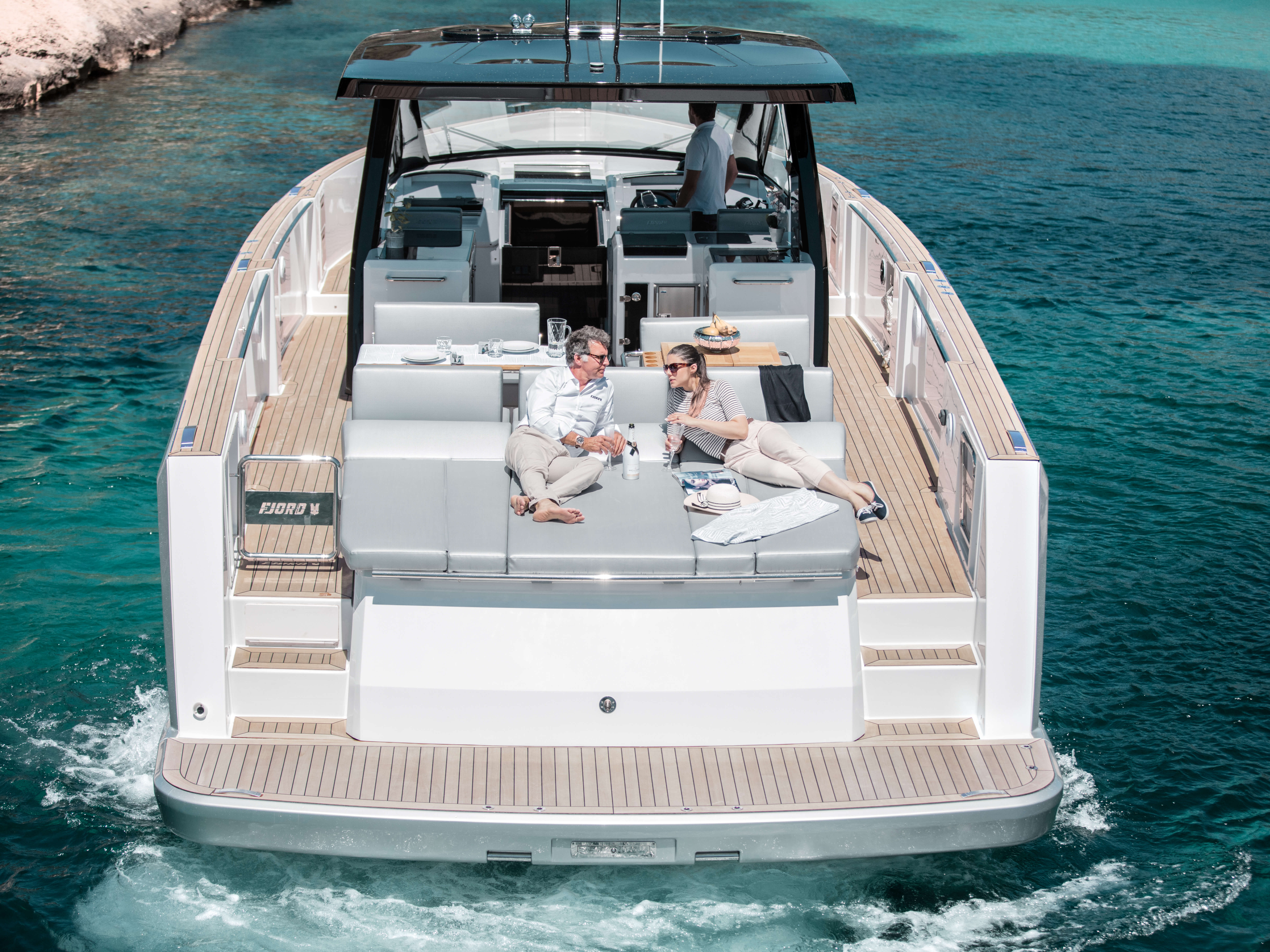 Fjord 48 open Exterior ride | bathing platform with teak and hydraulic lift, aft sunbed, ladder connecting main deck with bathing platform, stand alone bathing ladder with handles | Fjord
