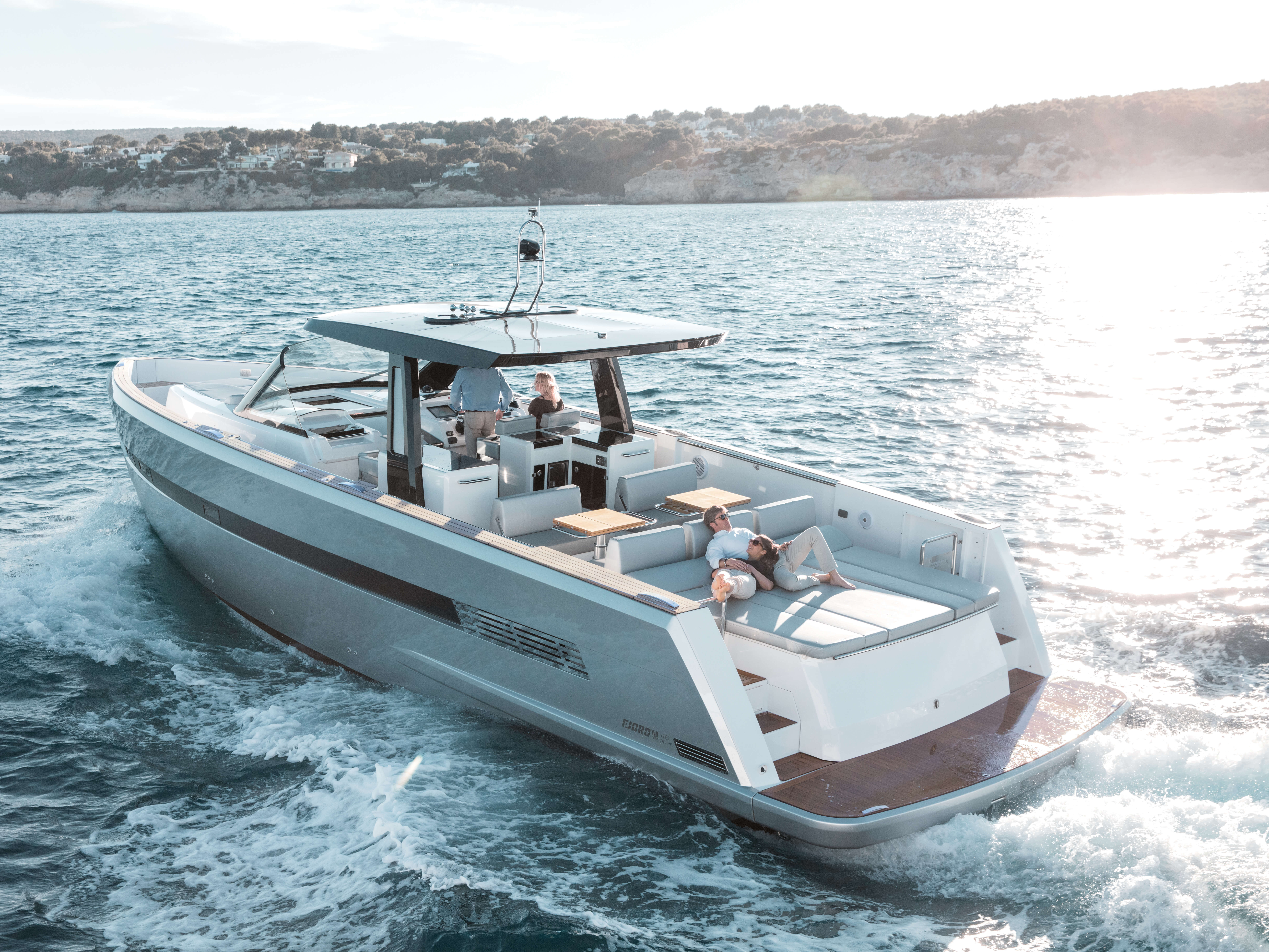 Fjord 48 open Exterior ride | painted hull, T-top with skylights, sitting area with foldable table convertible to sunbed, aft sunbed, bathing platform with teak and hydraulic lift, ladder connecting main deck and bathing platform | Fjord