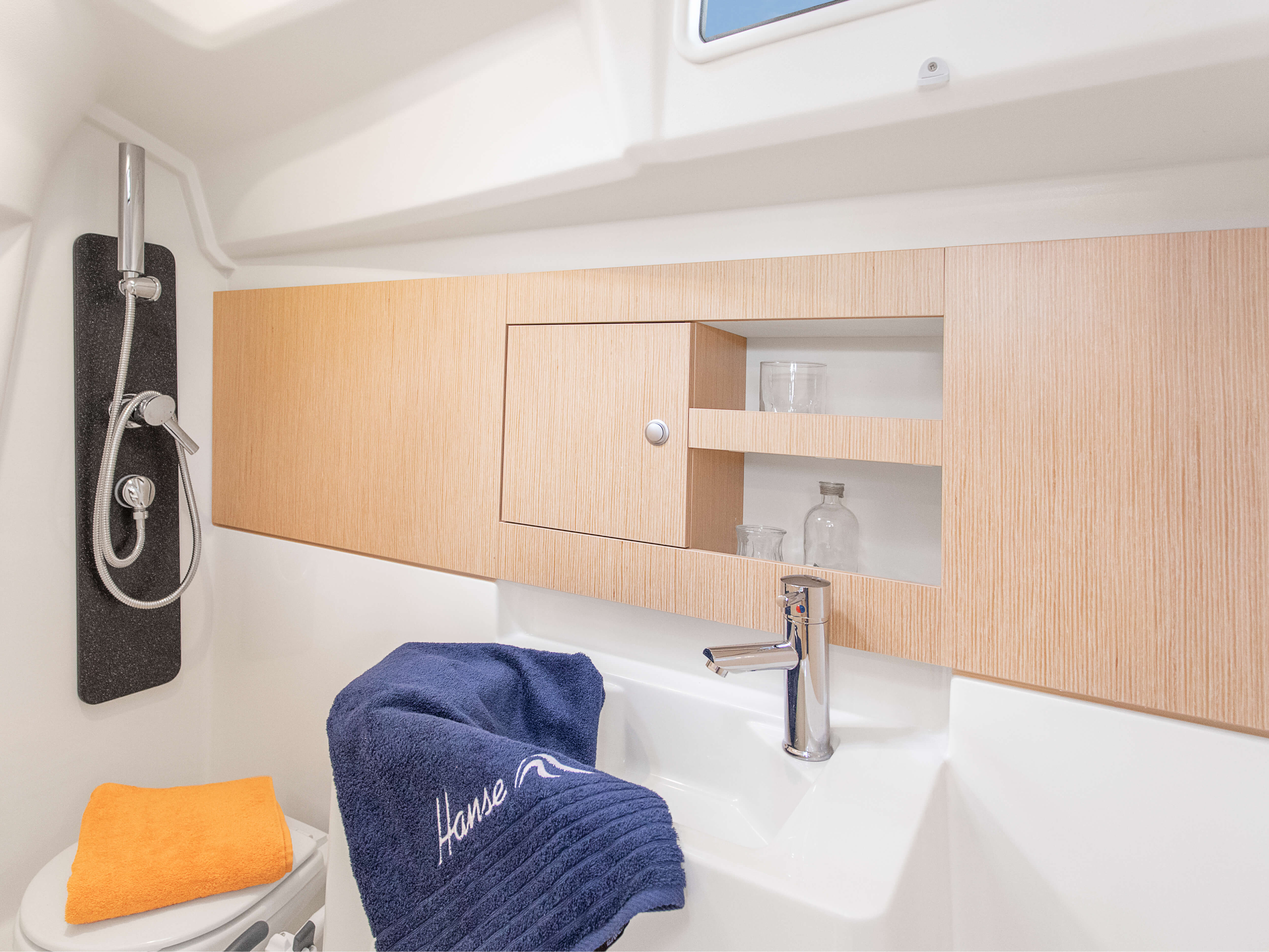 Hanse 315 Interior view wet cell | Thanks to various layout variants and a large selection of combination options – with high-quality fabrics, fine woods, trendy colours, select floorings and stylish furnishings – you can make your HANSE your own, a very personal one-of-a-kind yacht. | Hanse