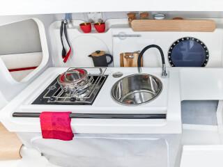 Dehler 30 one design mutfak | Donanımlı mutfakta bir gazlı ocak, lavabo ve ayak pompalı esnek musluk yanısıra, standart boyutta soğutucu için yer bulunur. | Dehler