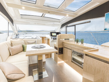 Sealine C390 saloon | The highly versatile saloon furniture includes an L-shaped sofa with chaiselongue function, a double pilot seat and a co-pilot bench. | Sealine