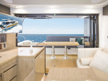 Sealine C390 saloon | Cockpit and saloon are connected by a bifold door and tilt-up window. Open both to enjoy one-level living on sunny days or panoramic views when they are closed. | Sealine
