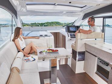 Sealine C390v salon | Le mobilier du salon, très polyvalent, comprend un canapé en forme de L transformable en chaise longue, un double siège de pilote et une banquette de copilote. | Sealine