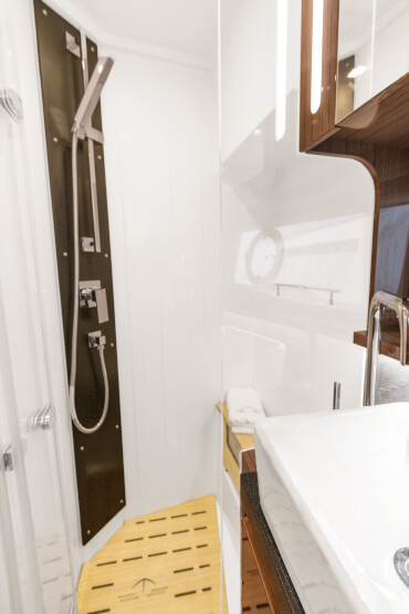 Sealine C430 bathroom | The shimmer of high-gloss wood is the binding element between the bathroom and cabin. | Sealine