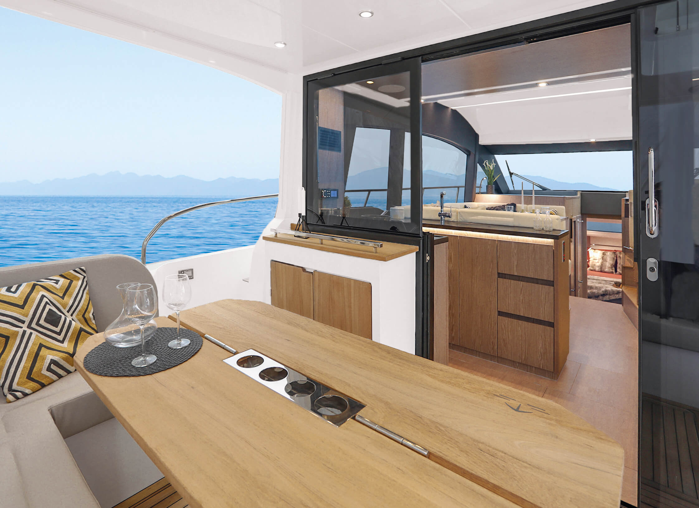 "Sealine F430 | Sliding door between cockpit and galley and tilting window to enlarge galley into cockpit. Seating ""L""-shaped bench with fixed backrest with storage underneath and teak bar. 