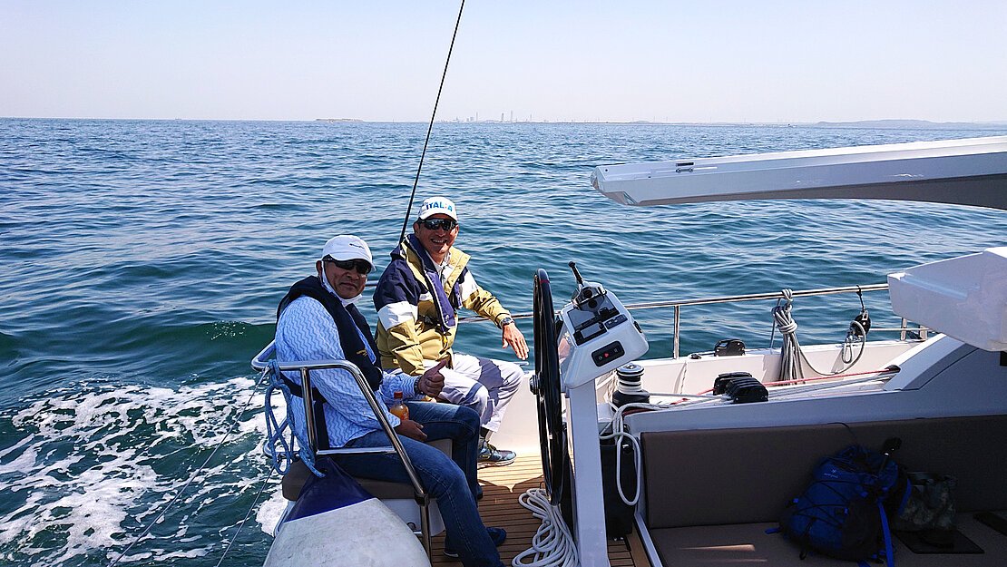 Bluewater sailing friends at the wheel of their yacht